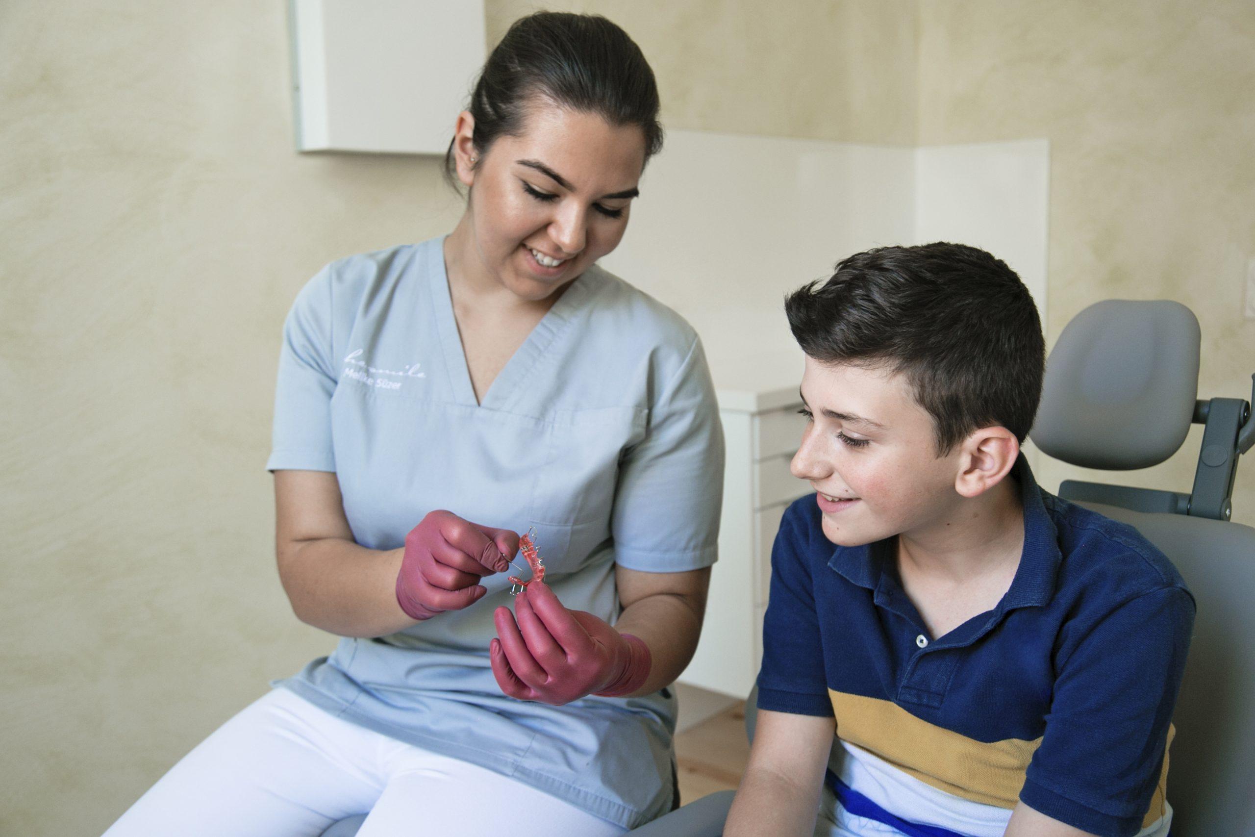 Zahnarzthelferin zeigt Patient Zahnspange